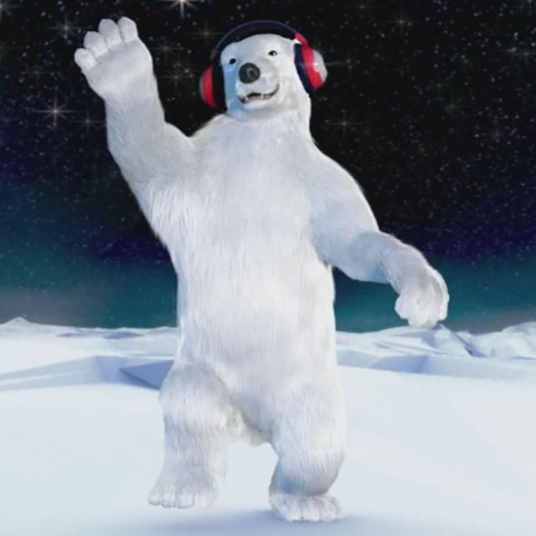 A photo-realistic CGI polar bear dances on arctic ice whilst wearing headphones, under a dark and starry sky.